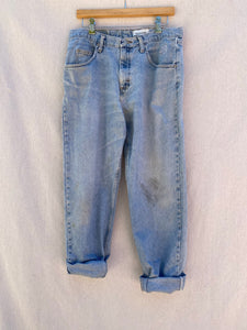 FRONT IMAGE OF FADED AND STAINED BLUE JEANS WITH CUFFED HEM.