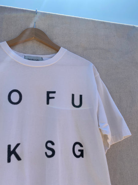 ZOOMED IN VIEW OF T-SHIRT'S UPPER FRONT LEFT. PRINTED LETTERS  OFUKSG ALSO VISIBLE.