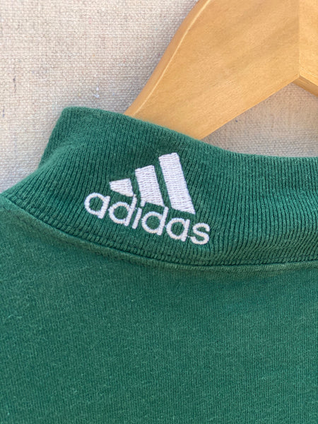 ZOOMED IN IMAGE OF ADIDAS EMBROIDERY AT MOCK NECK. EMBROIDERY IS IN WHTE.