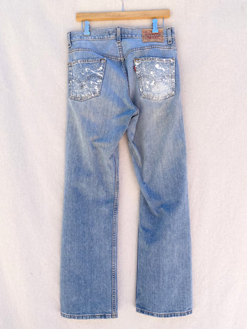 BACK VIEW OF FADED BLUE LEVI'S JEANS WITH PAINT SPLATTER POCKETS.