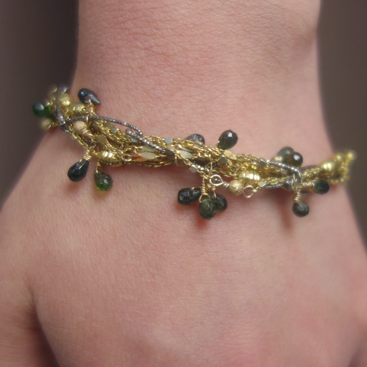 I've Seen Fire and Rain: emerald, gold, and silver bracelet