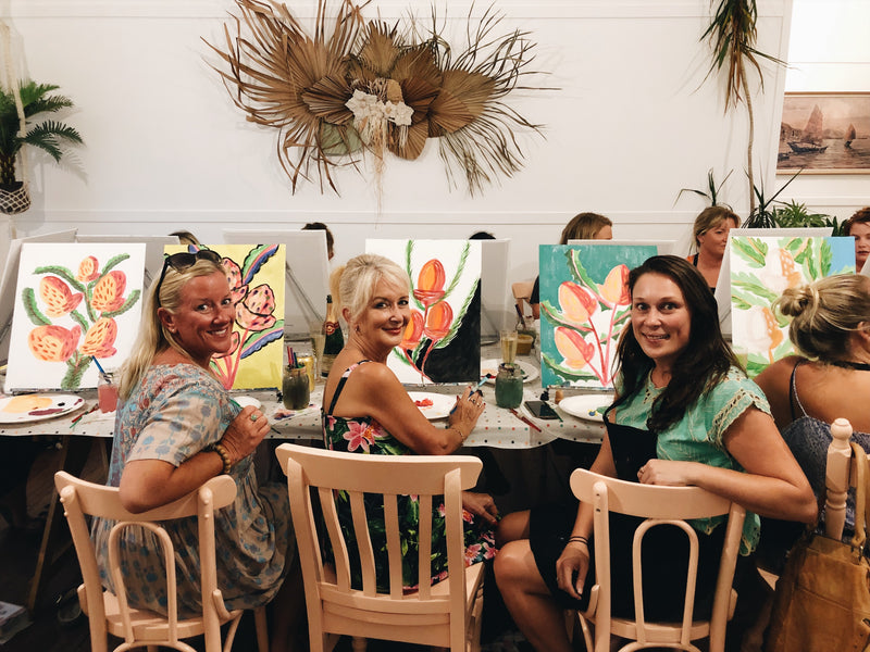 Three ladies painting native flowers during botanical paintings workshop