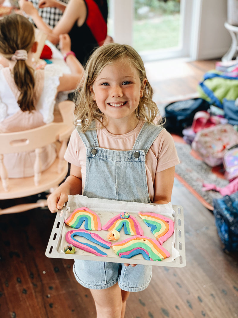 Smiling girl with rainbow coloured handmade pottery pieces