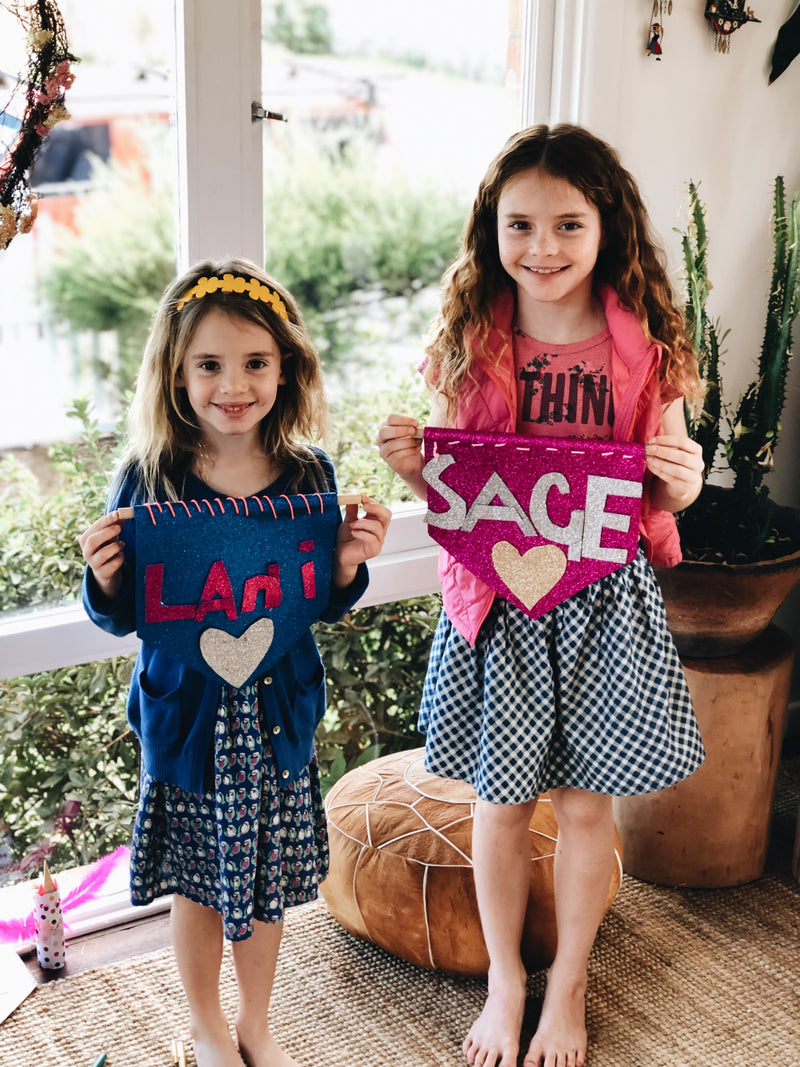 Two young girls with their handmade name signs