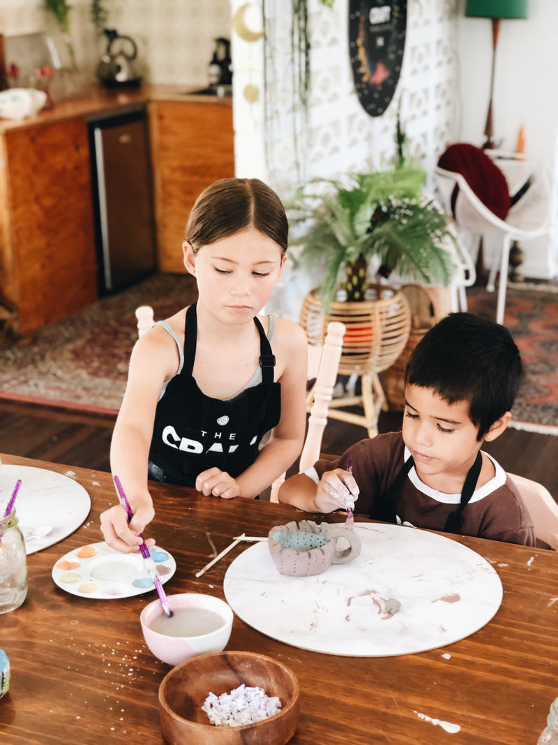 Two young kids making mugs from clay at The Craft Parlour pottery workshop