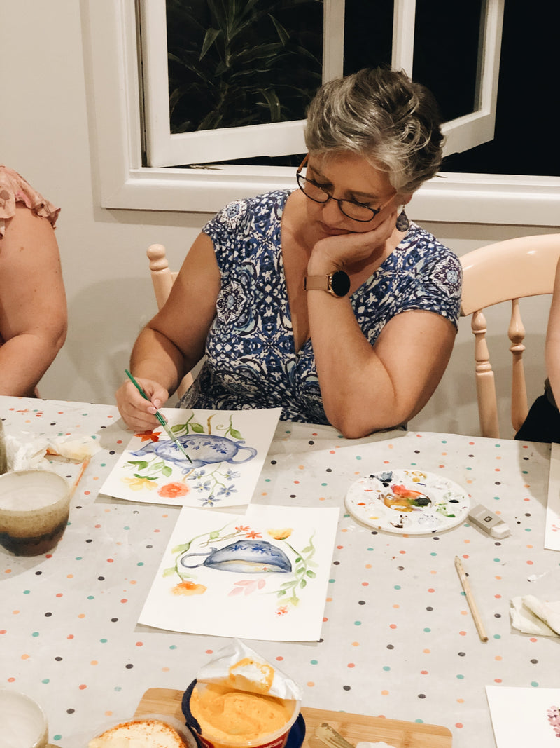 Lady finishing her gorgeous watercolour painting of a blue teapot