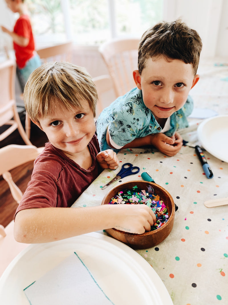 Two young boys making craft at after school craft club