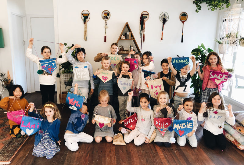 Group of kids with handmade name signs at The Craft Parlour craft day