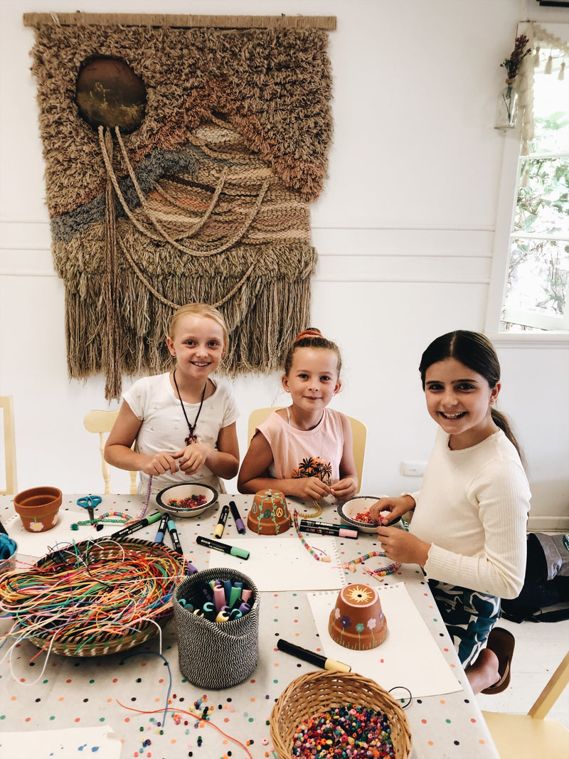 Three girls making bead necklaces during Gold Coast craft day