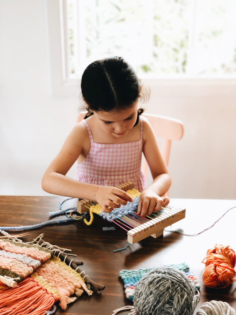Child braiding her loom weaving kit at Gold Coast craft workshop