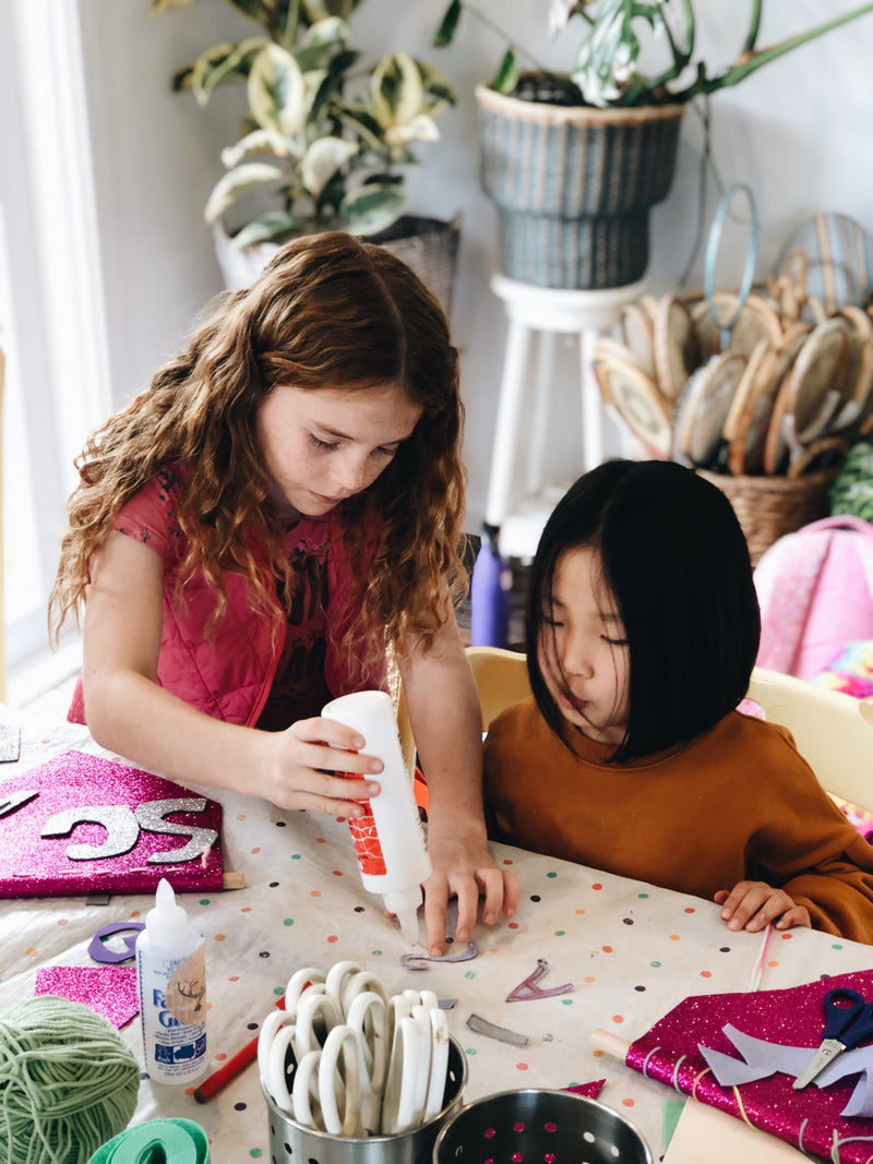 Two girls making name flags during The Craft Parlour craft day
