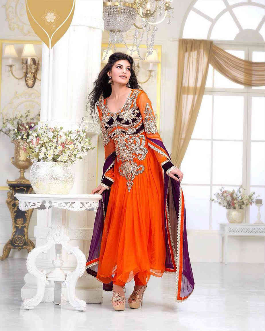 Go Bold with this Eye-Catching Saffron Net based Gorgeous Anarkali Suit. The Saffron Color is beautifully contrasted and balanced with a dash of black. Striking Golden embroidery work is simply outstanding. Long symmetric neck work looks absolutely eye-catching. Beautiful work is done on the sleeves and the back side. You surely will look like a princess in this extra-ordinary attire. It is provided with an equally beautiful Chiffon Dupatta and shantoon Churidar.