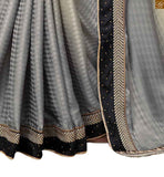 Grey and Cream jacquard heavy embroidered saree with stone work and Black blouse made of net with long sleeves. Embroidered butta on sleeves is provided and embroidered border line on lower part Image