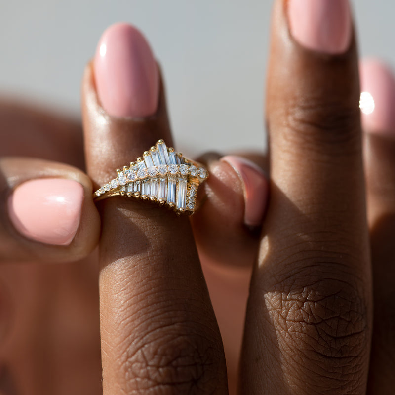 Asymmetrical-Baguette-Cluster-Ring-with-Round-Diamond-Beams-closeup-on-finger
