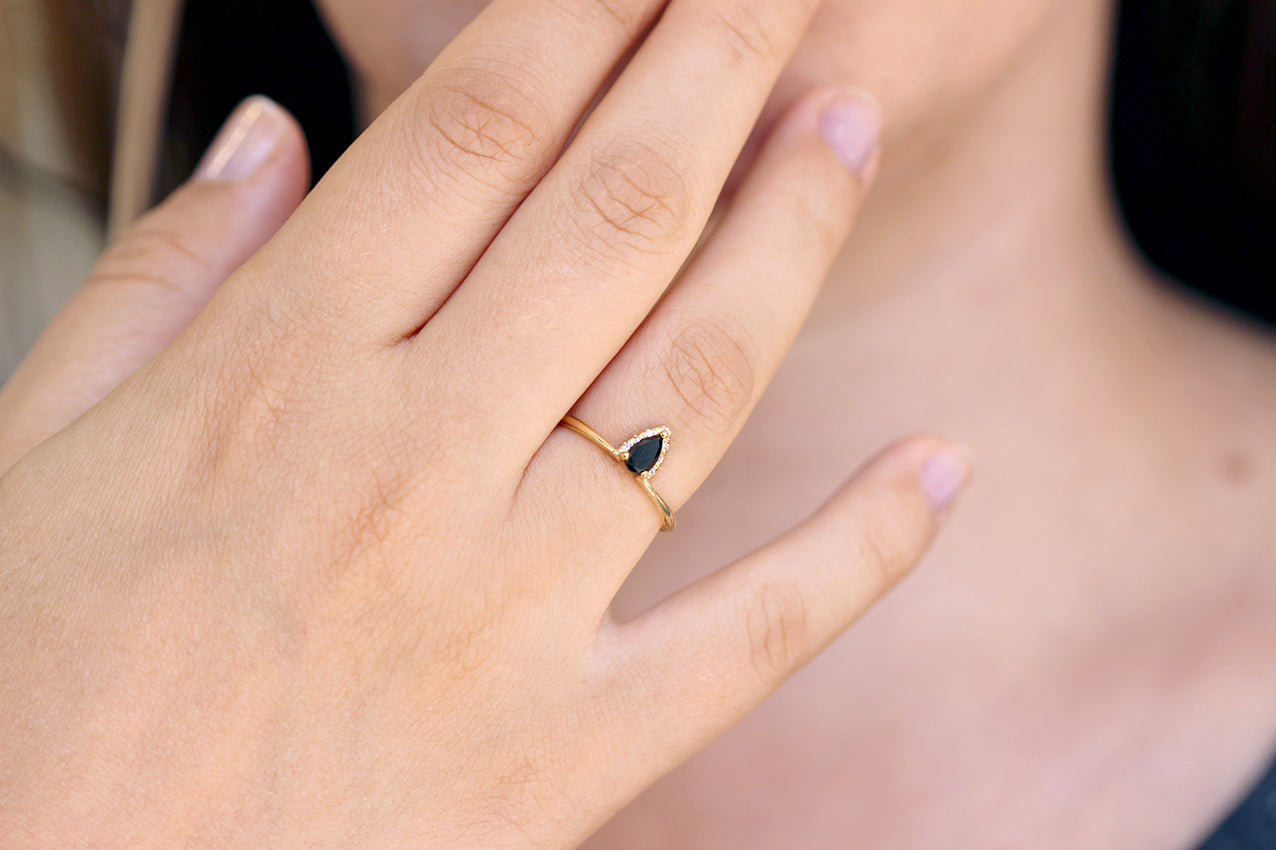 Black Diamond Pear Engagement Ring With White Diamond Accents on finger