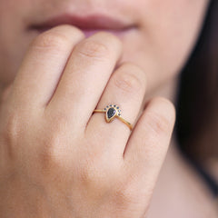 Black Pear Diamond Engagement Ring with Half Diamond Halo on hand up close