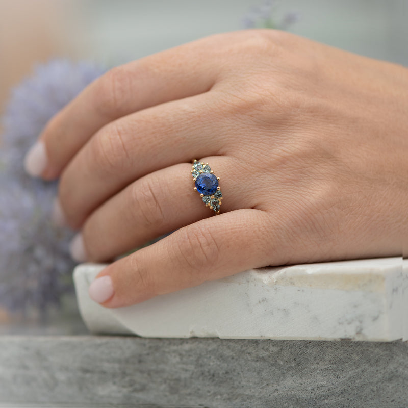 Blue-and-Teal-Sapphire-Cluster-Ring-in-finger