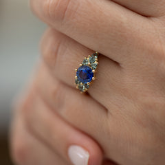 Blue-and-Teal-Sapphire-Cluster-Ring-on-finger-closeup