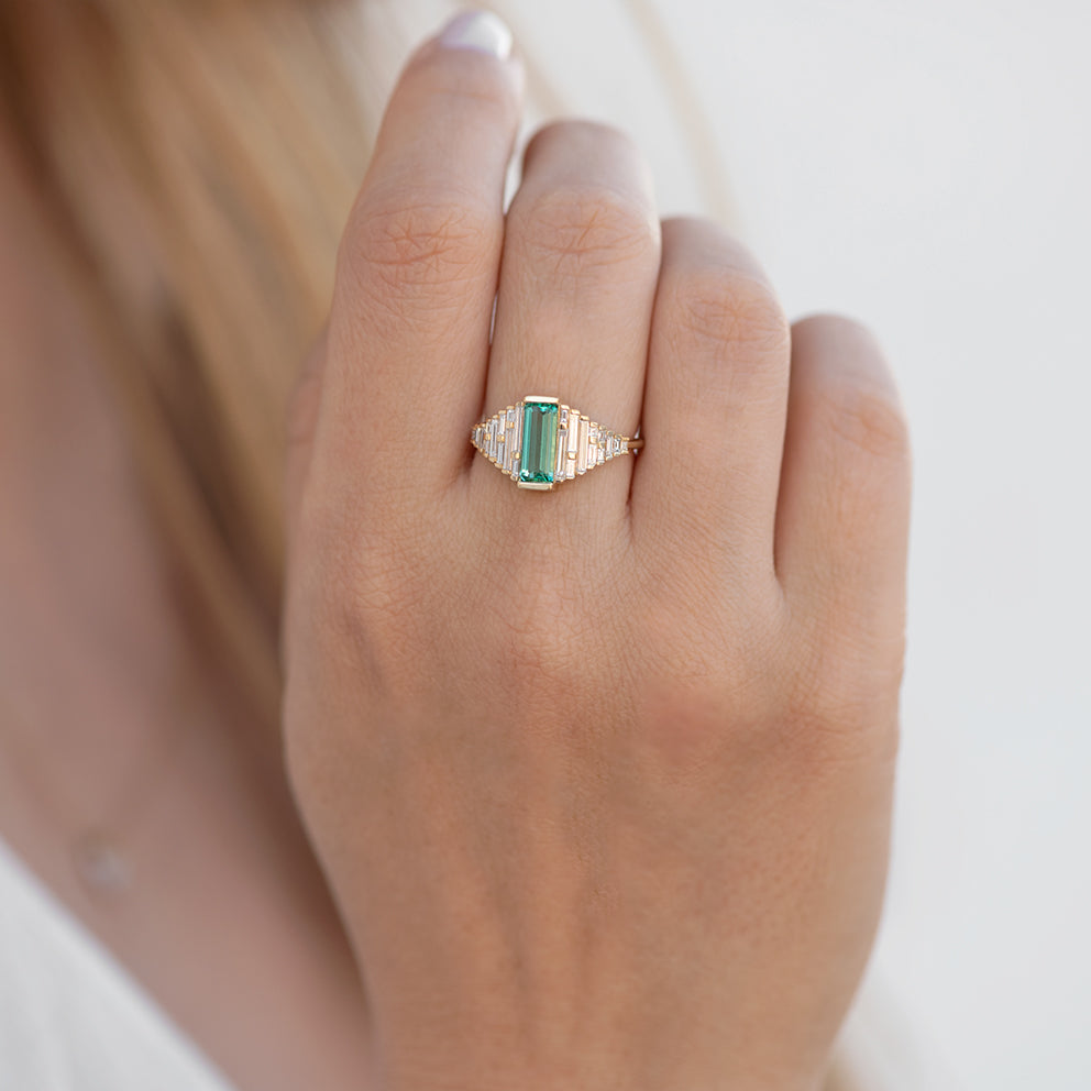 Emerald Ring with needle baguette Diamonds on finger