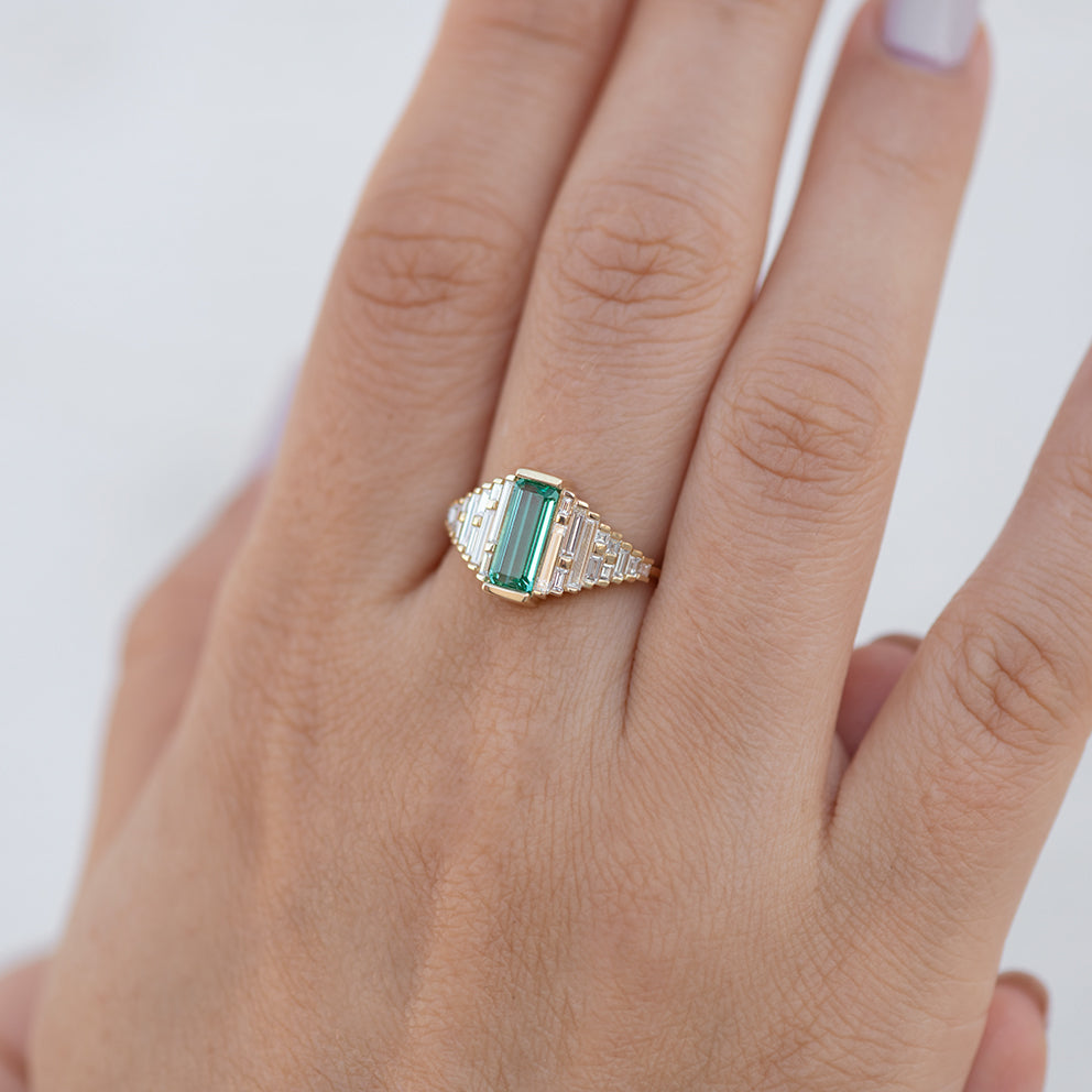 Emerald Ring with needle baguette Diamonds one hand.jpg