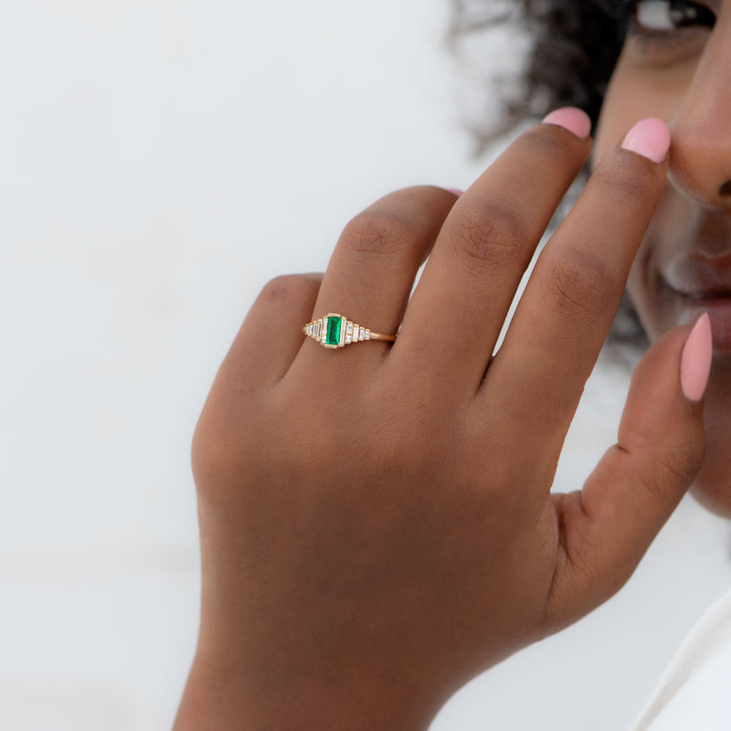 Dainty-Emerald-Engagement-Ring-with-Needle-Baguette-Diamonds-ON-FINGER