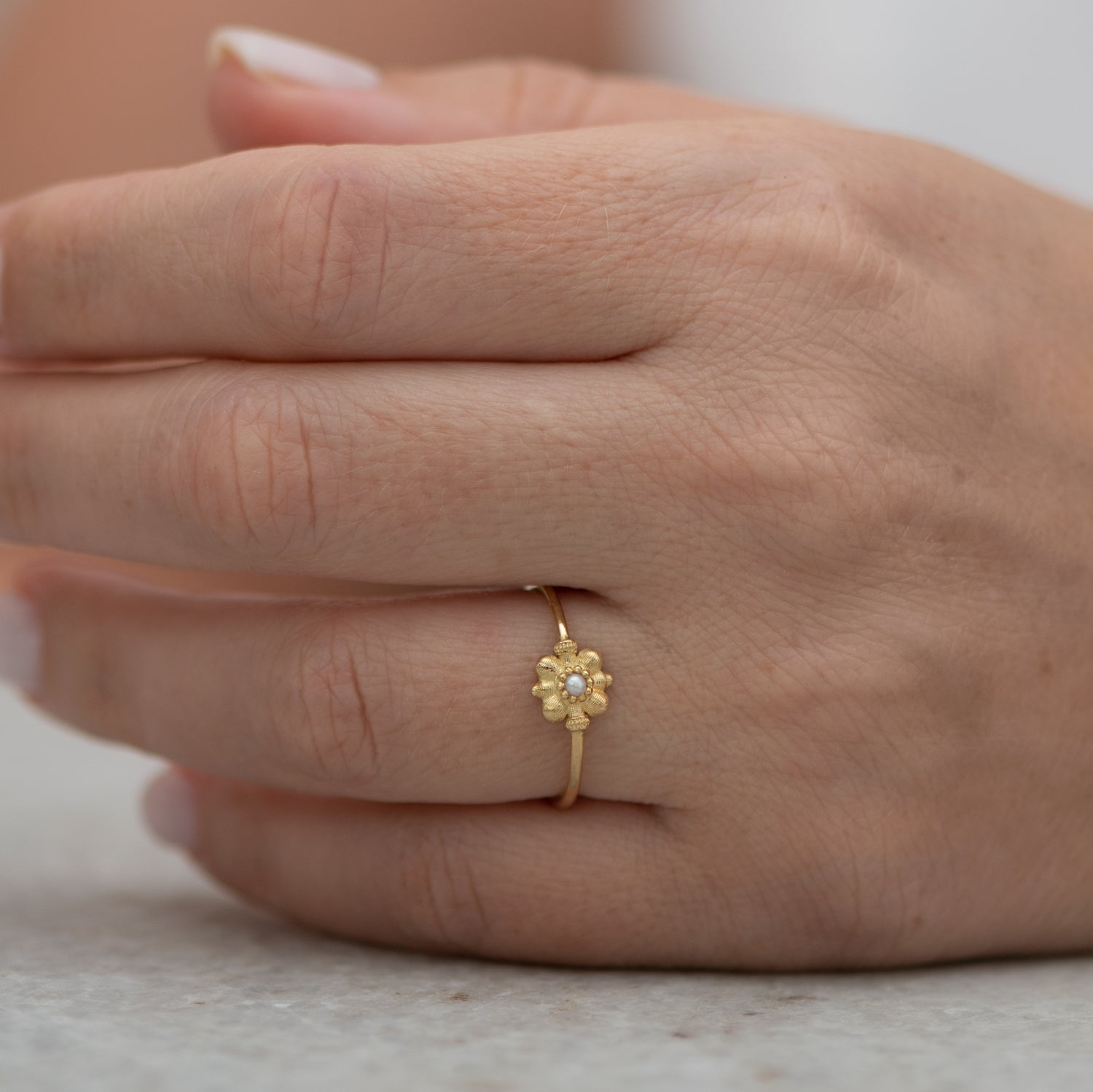Dainty-Gold-Flower-Ring-Seed-Pearl-Ring-top-shot-on-finger