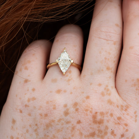 Diamond-Rhombus-Engagement-Ring-with-Triangle-Cut-Diamonds-close-up-om-hand