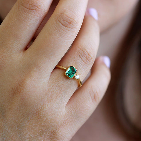 Emerald Engagement Ring with A Small Diamond On Finger