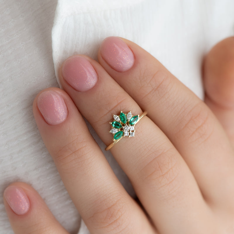 Emerald-and-Diamond-Cluster-Engagement-Ring-on-finger