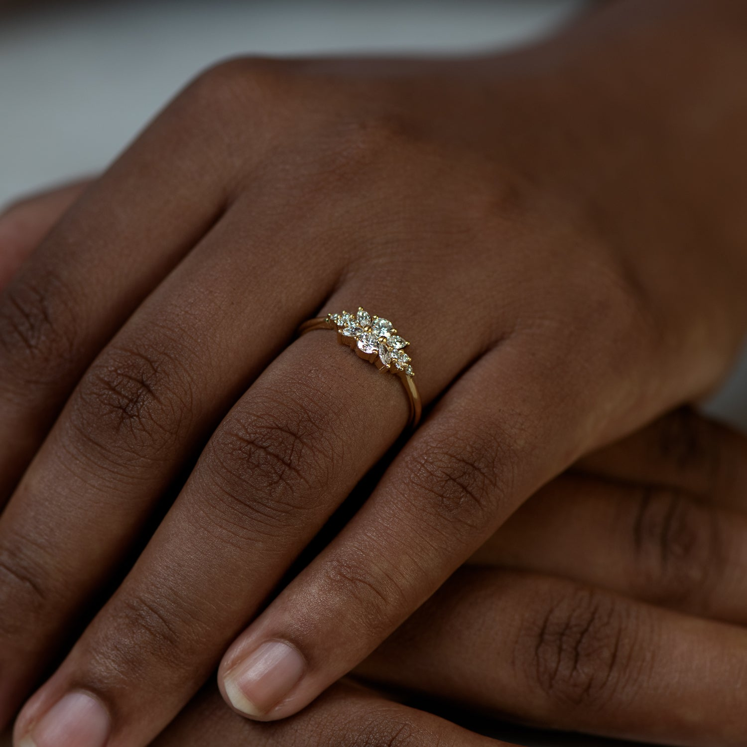 Engagement-Ring-with-a-Cluster-of-Diamonds-Small-Flora-Ring-on-finger