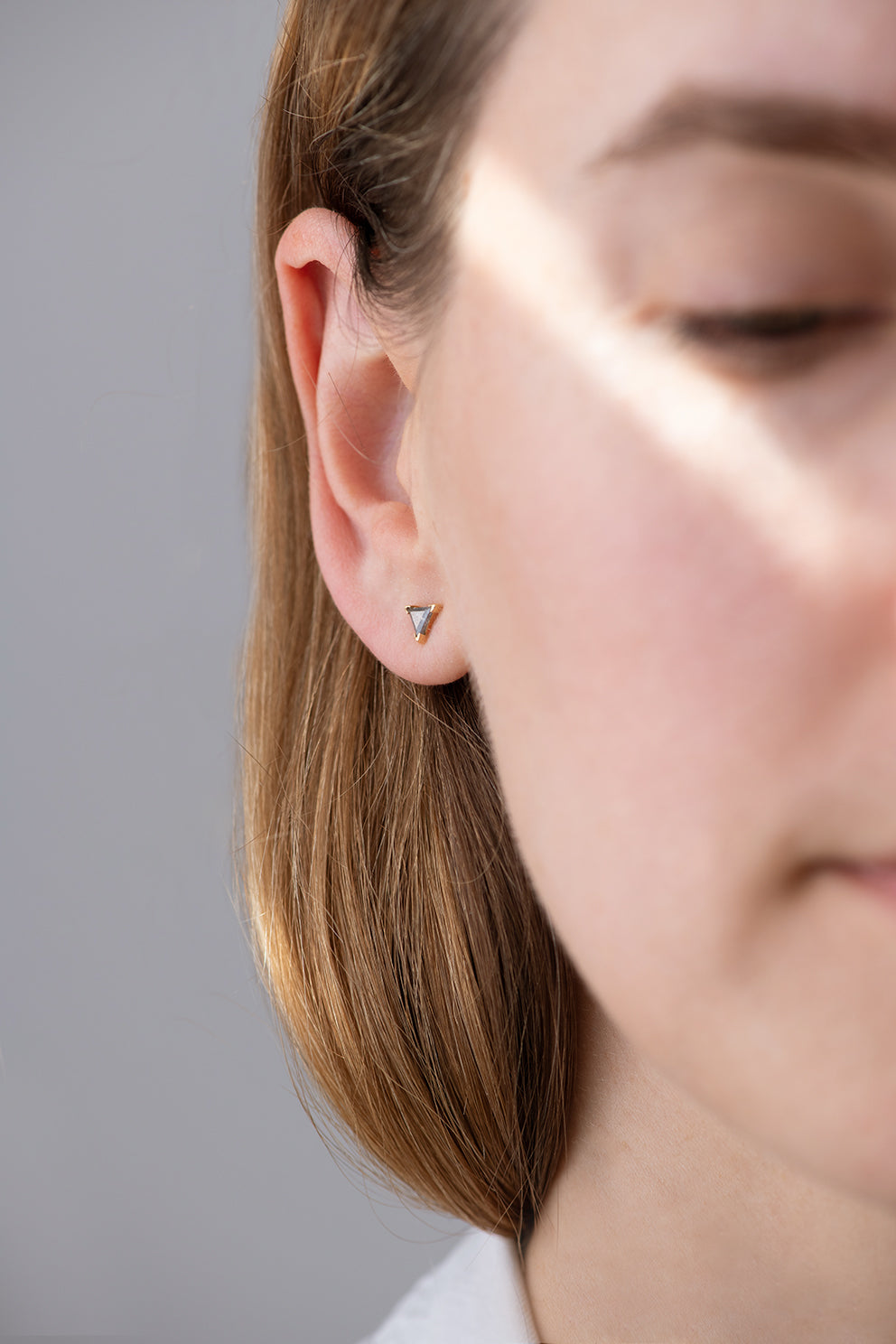 Grey Triangle Diamond Stud Earrings other angle on ear