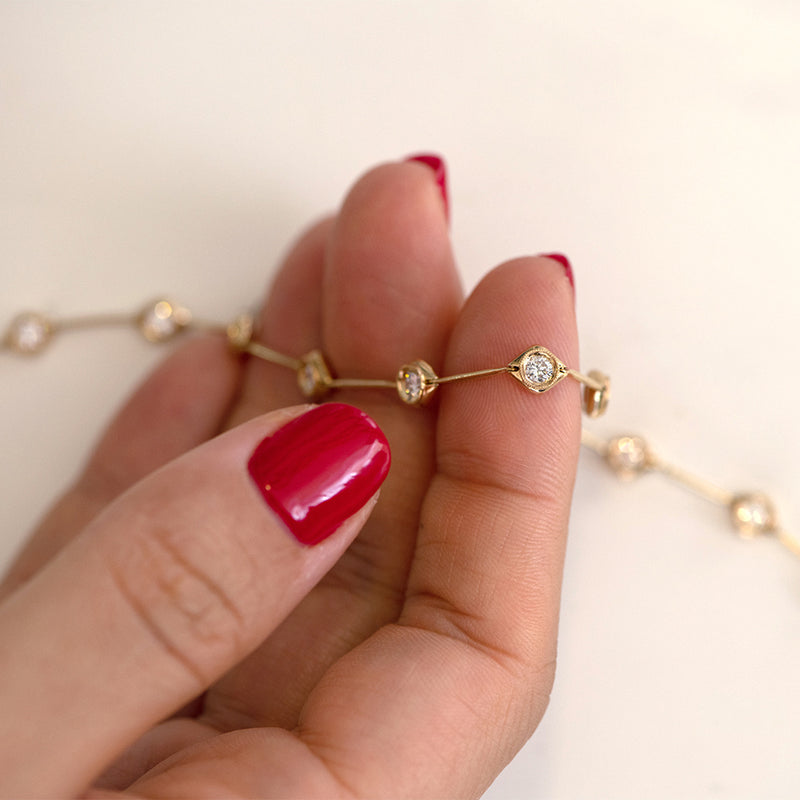 Minimalist-Daisy-Chain-Gold-Bracelet-with-White-Diamonds-holding-hand-closeup