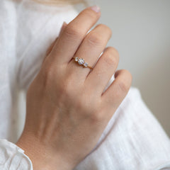 Three Stone Engagement Ring Floating on a Gold Wave on shoulder.