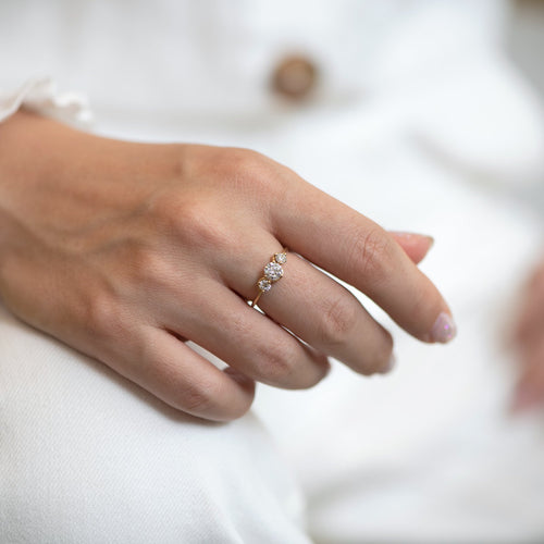 Three Stone Engagement Ring Floating on a Gold Wave on lap
