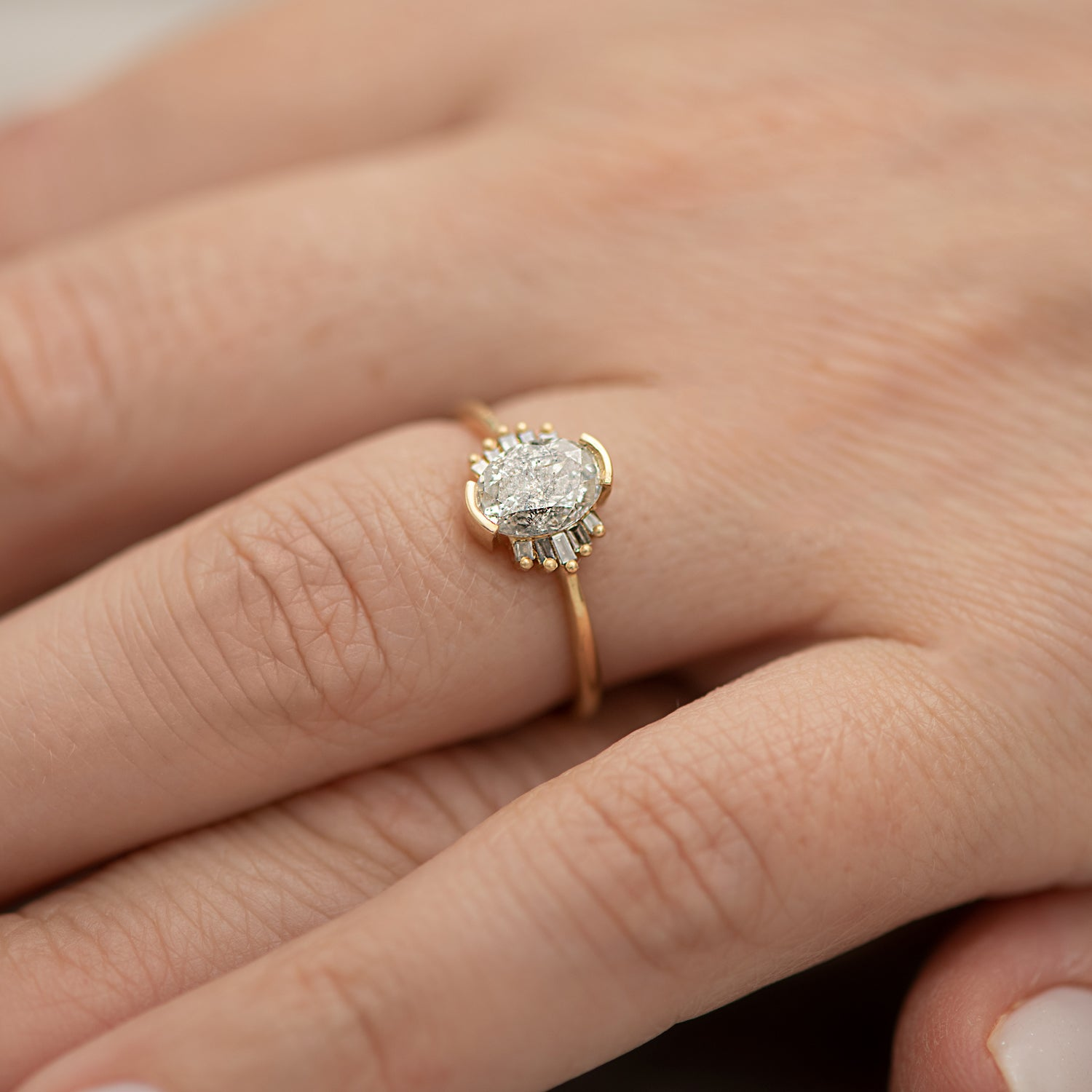Oval-Cut-Salt-and-Pepper-Diamond-Engagement-Ring-with-Baguette-Frills-on-hand