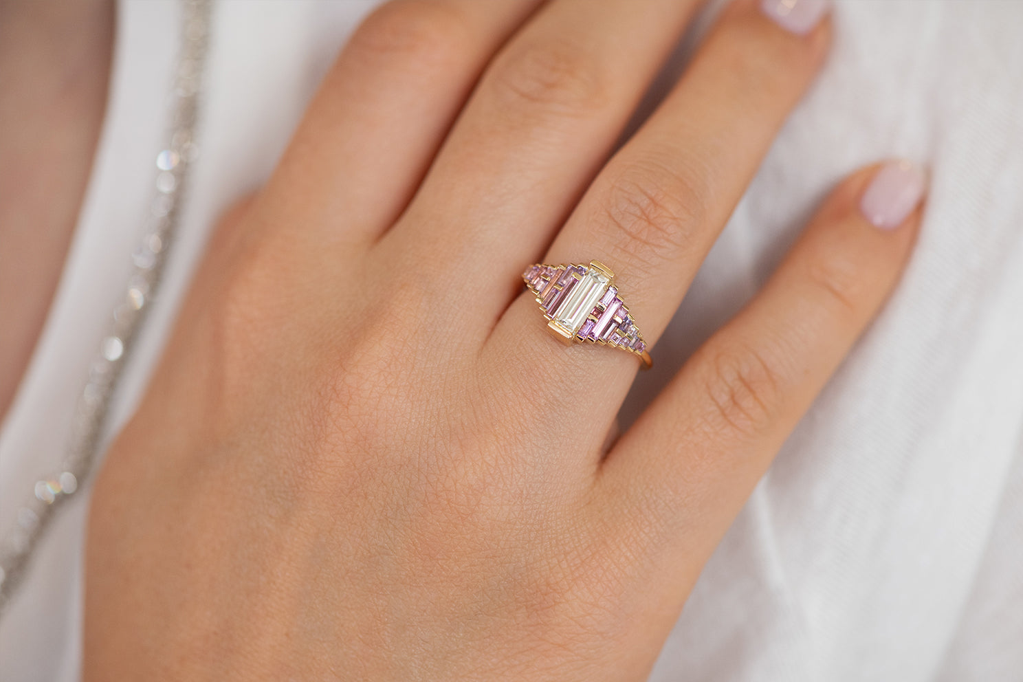 Purple and Lilac Sapphire Ring with Baguette Diamond on Hand in Sun