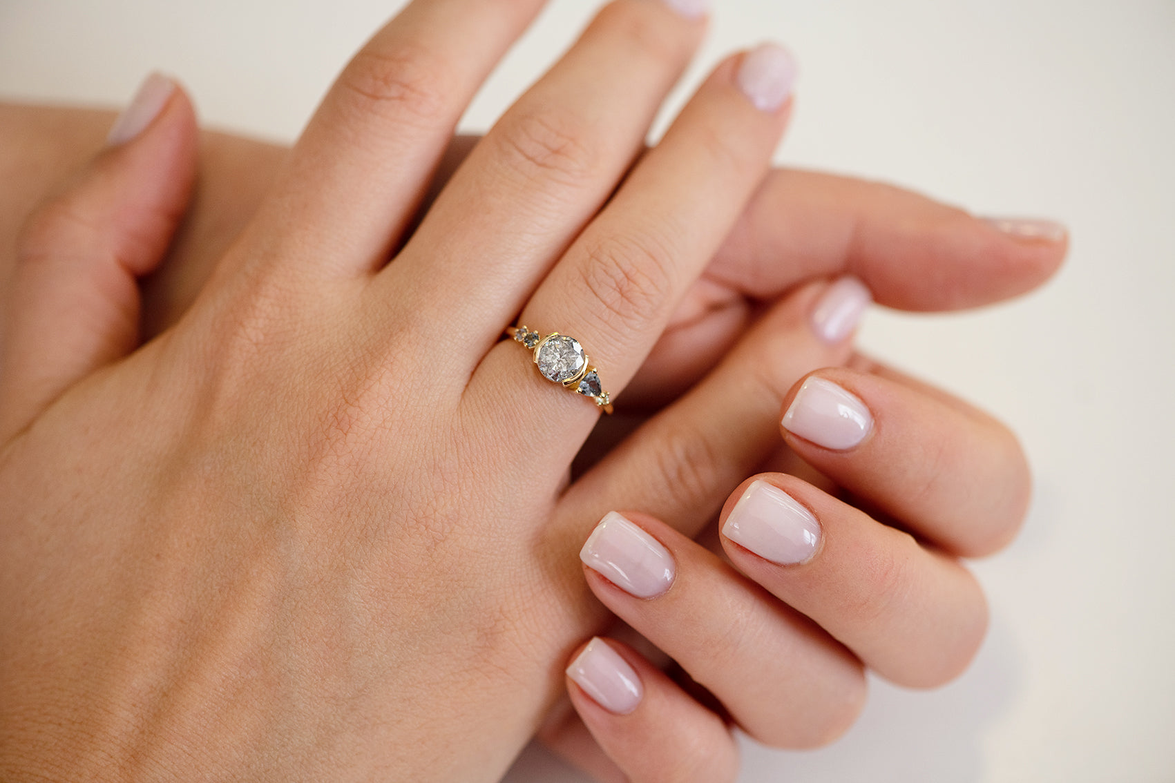 Sapphire und Diamond Engagement Ring in Teal und Grey auf Hands