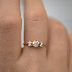 Three Stone Engagement Ring Floating on a Gold Wave floating finger up close
