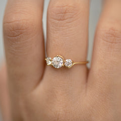 Three Stone Engagement Ring Floating on a Gold Wave floating finger on side