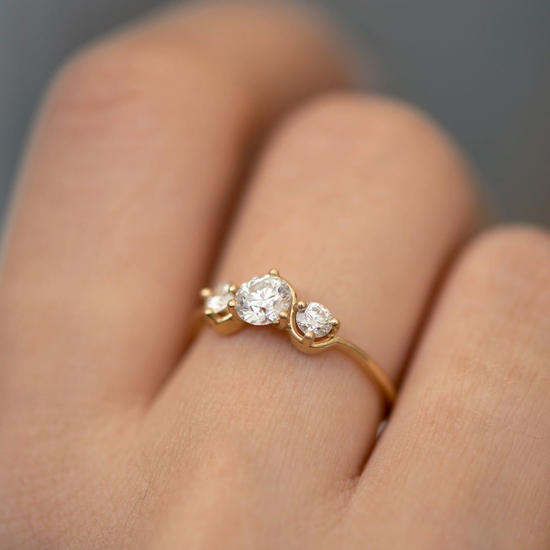 Three Stone Engagement Ring Floating on a Gold Wave up close.jpg