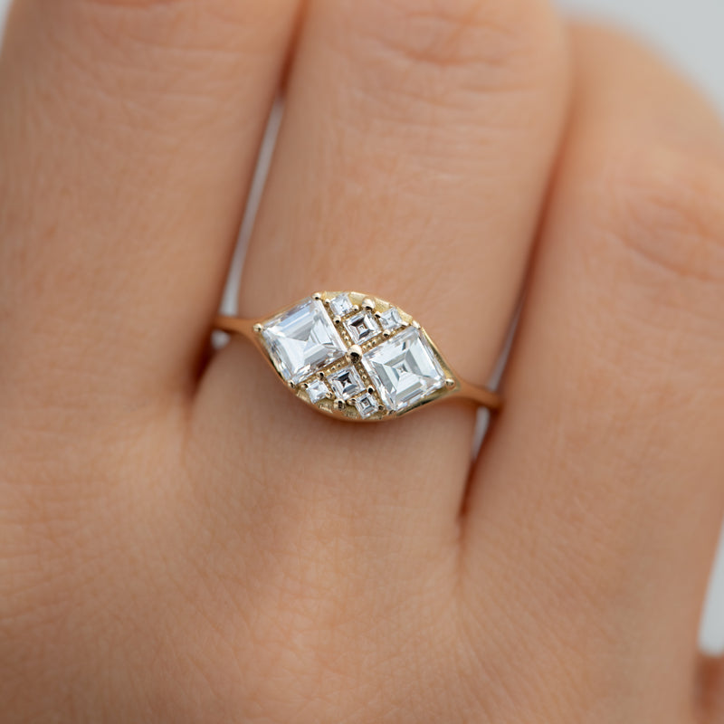 Step-Cut-Engagement-Ring-with-Eight-Square-Diamonds-closeup-on-finger