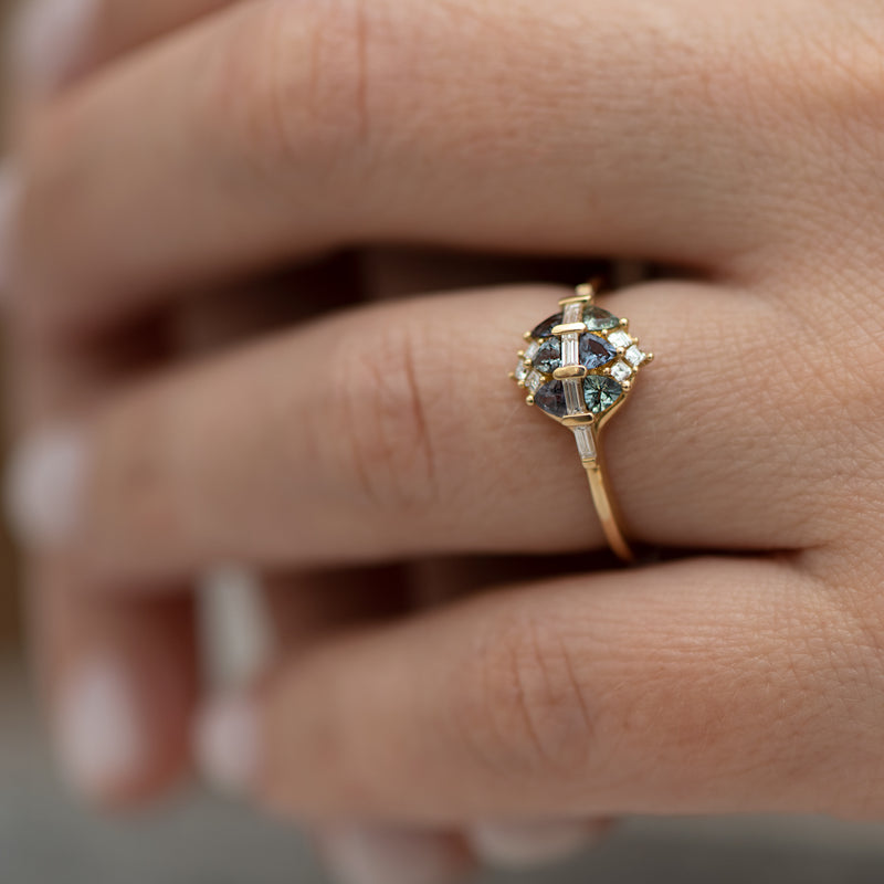 Teal-Sapphire-and-Diamond-Cluster-Engagement-Ring-side-shot-on-finger