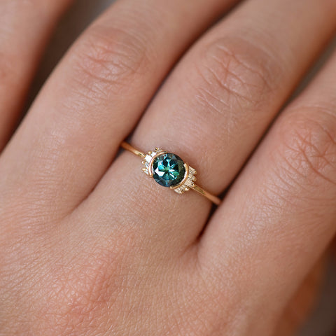 Teal Sapphire Ring with Baguette Diamond Wings on Hand up close detail shot