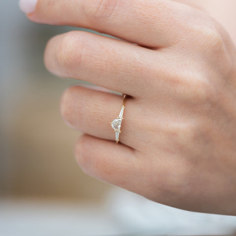 Three-Stone-Engagement-Ring-with-Half-Moon-and-Baguette-Cut-Diamonds-closeup-on-finger