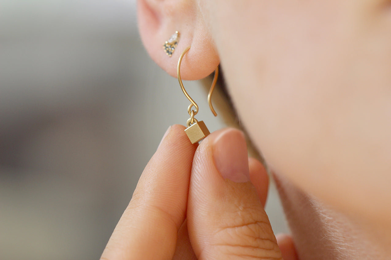 Tiny Cube Gold Earrings Between Fingers