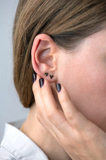 Triangle Earrings with Black and White Diamonds on ear in other view