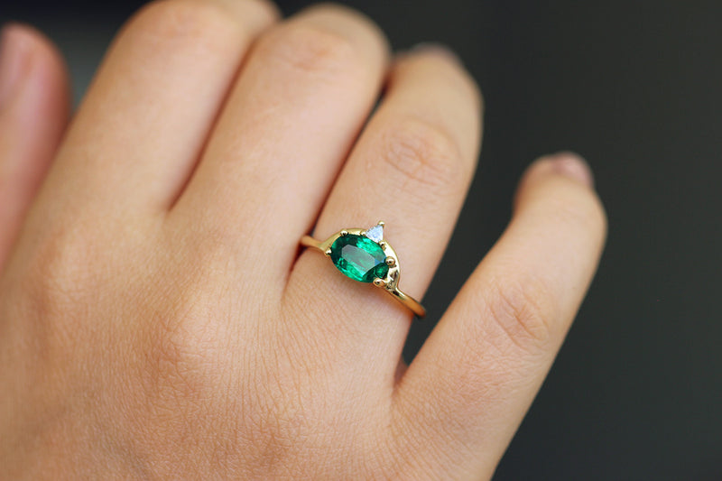 oval emerald Engagement Ring on finger