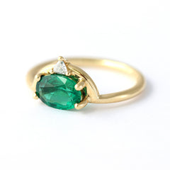 emerald engagement ring with trillion diamond