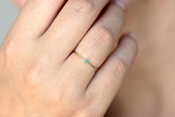 thin gold emerald ring on hand