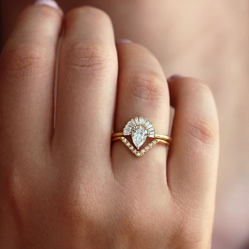 pear diamond engagement ring set with baguette diamond crown and chevron wedding band close up on hand